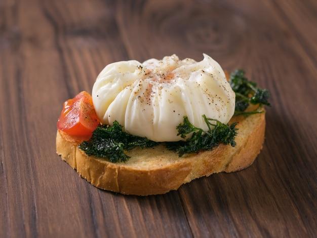 木製のテーブルの上のパンにトマトとローストハーブのスライスとポーチドエッグ。ポーチドエッグとベジタリアンスナック。