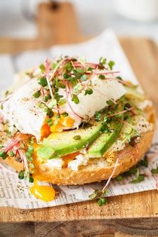 Яйцо-пашот с авокадо, сыром рикотта и ростками редиса на булочке для гамбургера