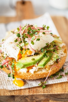 Poached egg with avocado, ricotta cheese and radish sprouts on burger bun