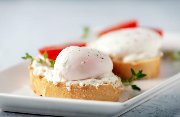 ポーチドエッグとチーズペーストとハーブのおいしい朝食健康食品