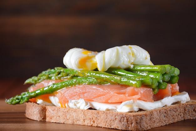 ポーチドエッグ、トーストにフライドアスパラガス、クリームチーズ、サーモン、スパイス。健康的なフランスの朝食のコンセプト
