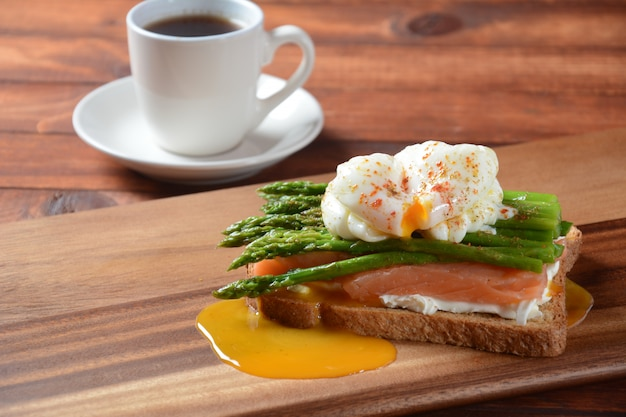 Poached egg with fried asparagus, cream cheese , salmon and spices on a toast. healthy french breakfast concept