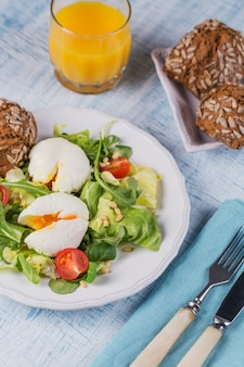 グリーンサラダ、トマト、全粒粉パン、青い木のオレンジジュースとポーチドエッグ。