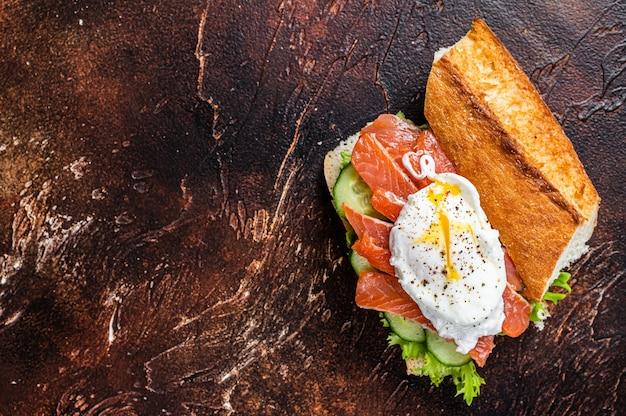 Яйцо-пашот с копченым лососем и авокадо на тосте. темный стол. вид сверху.
