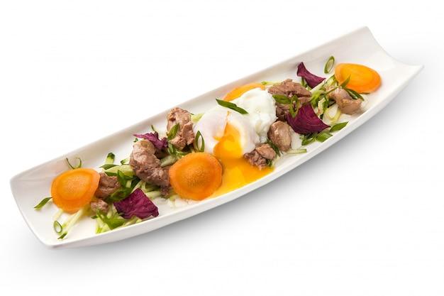 Яйцо-пашот с тунцом на продолговатой белой тарелке с овощами