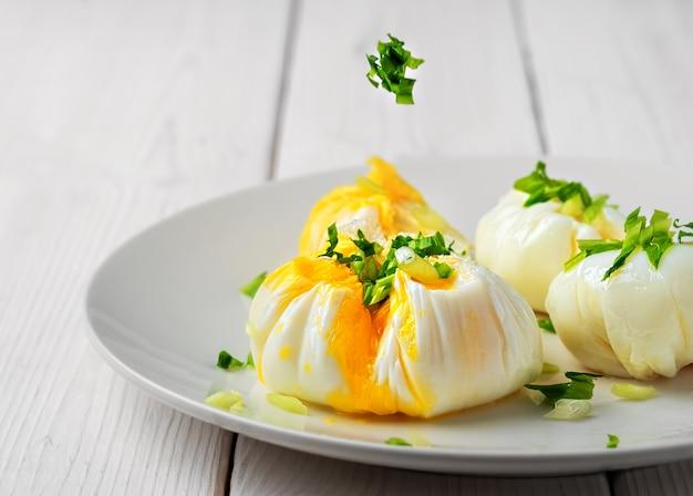 흰 접시에 신선한 허브로 장식 된 데친 달걀