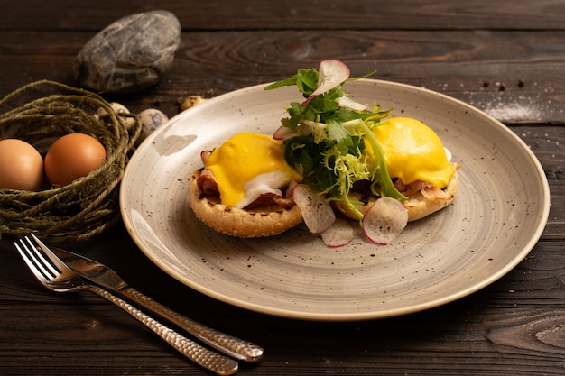 Poached eggs with bacon, radish, arugula and a burger bun are beautifully served on a dark wooden table.