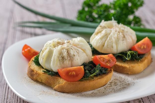 白い皿にパンとネギを添えたポーチドエッグ。ポーチドエッグとベジタリアンスナック。