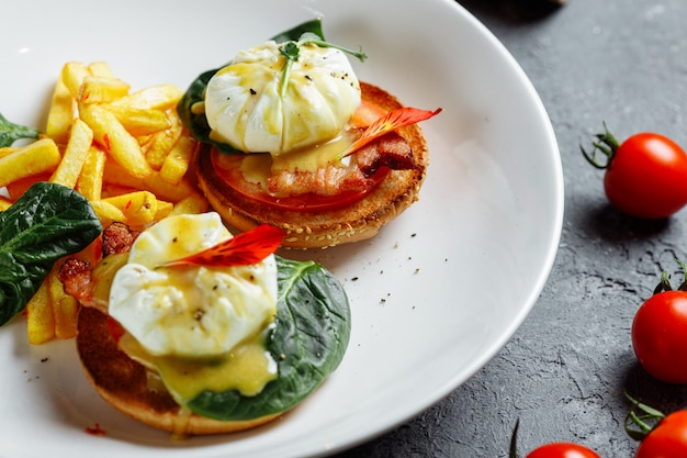 Poached eggs with french fries and bacon on toast