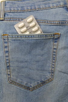 In the pocket of blue jeans inserted packing with pills.