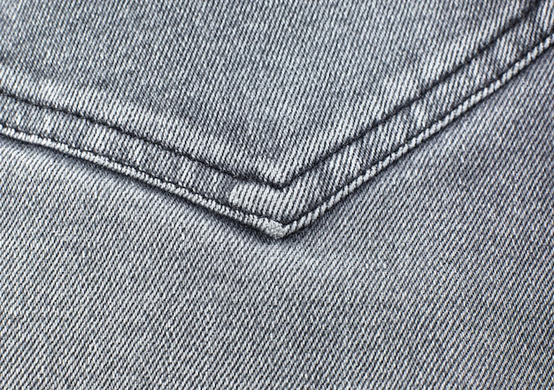 Pocket of grey hipster jeans material. gray cloth texture background.