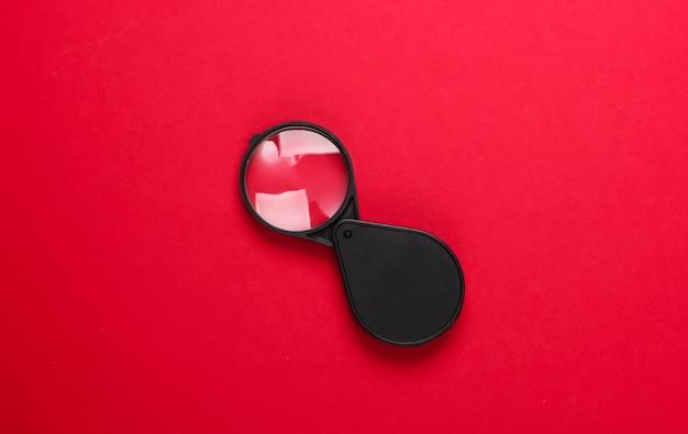 Карманная лупа на красном.