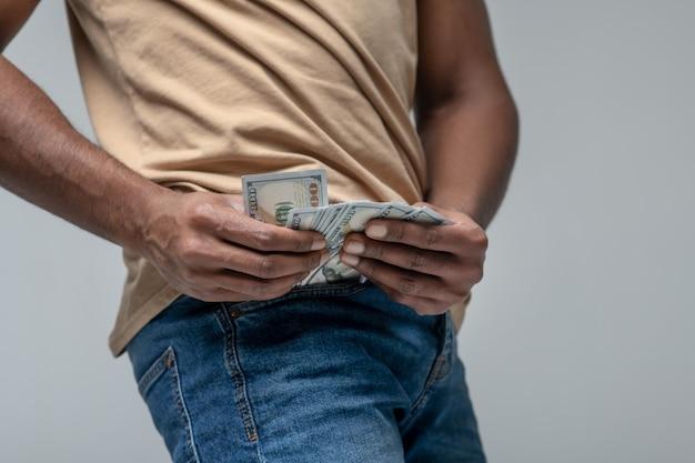 Карманные деньги. руки темнокожего мужчины вынимают банкноты из кармана джинсов, лица не видно