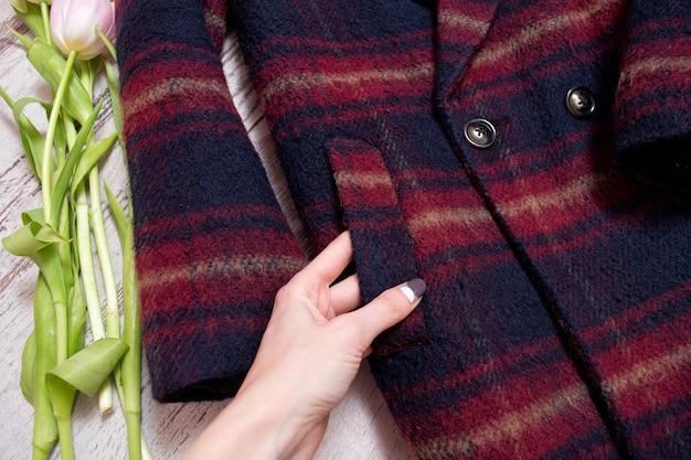 市松模様のコートのポケット、女性の手、チューリップ。ファッショナブルなコンセプト、ディテール