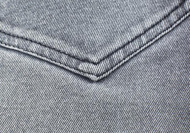 Карман из серого материала хипстерских джинсов. серая предпосылка текстуры ткани.