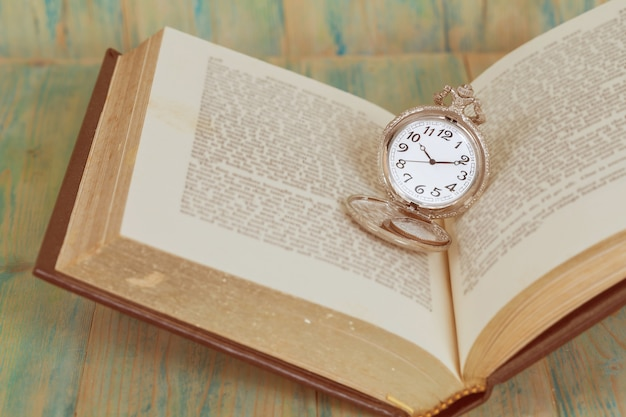 Pocket watch over age book background ,time concept