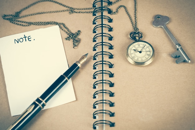 Pocket watch over book note on wood table .