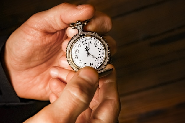 A pocket watch in the hands of a man