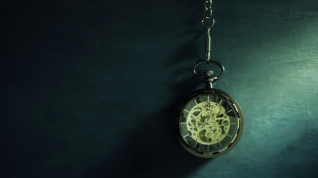 Pocket watch hanging on black chalkboard and sunlight in morning. concept of time and education.