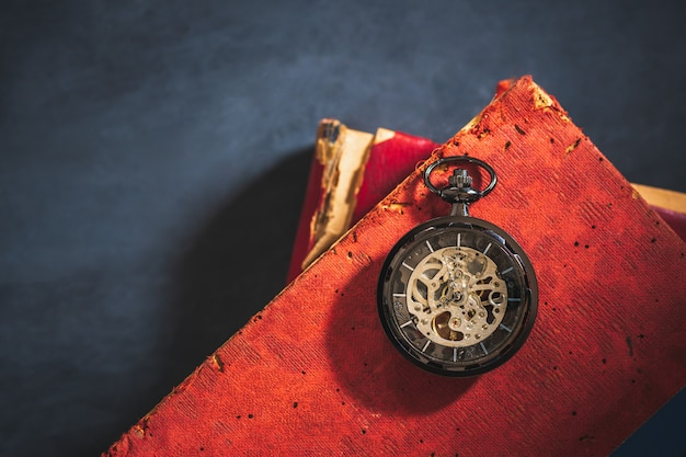 Pocket watch and old book on cement floor.
