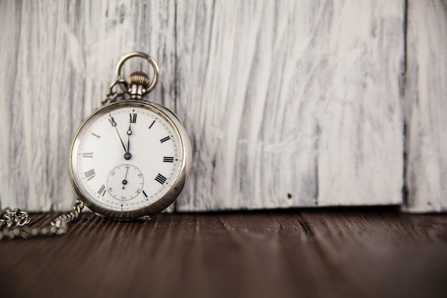 Pocket watch on old wooden background