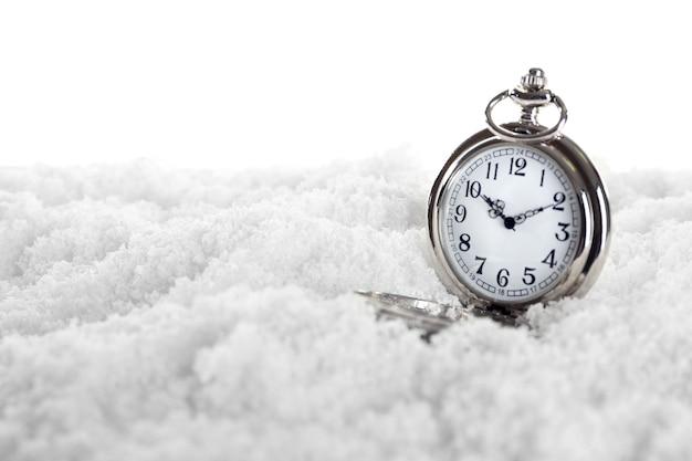白い雪の背景の懐中時計