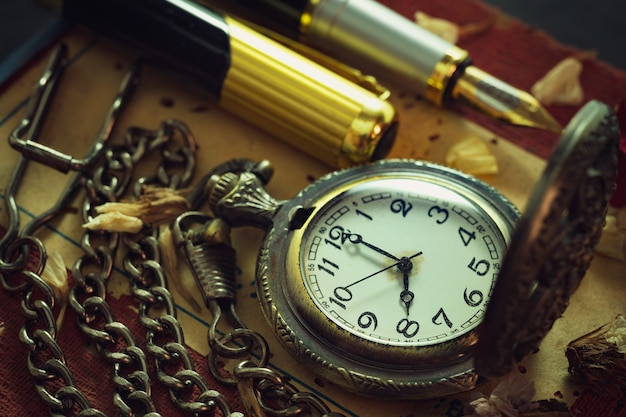 Pocket watch and pen on table.