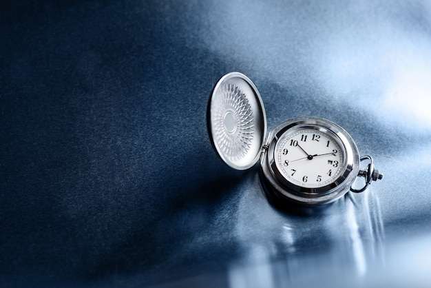 Pocket watch on a rough metal surface with copy space.