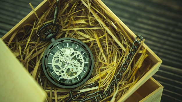 Pocket watch winder on natural wheat straw in a wooden box