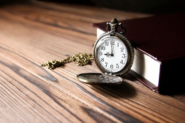 A pocket watch with book on wooden table