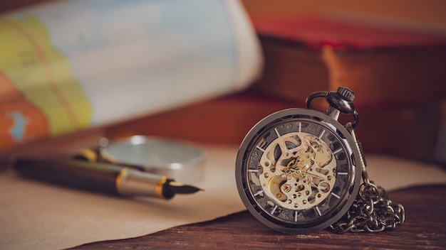 Pocket watch with old books and pen with paper map on the table by the window.