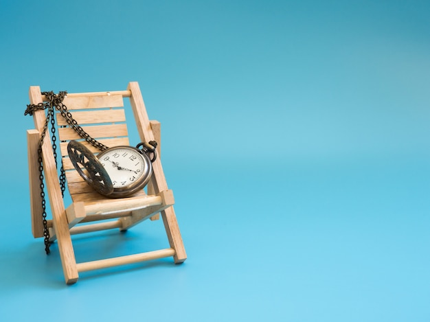 Pocket watch on the wooden beach chair on blue background