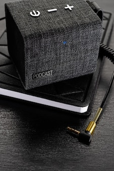Podcast concept. wireless, small column on the book (blonote) with an audio cable jack 3.5 mm.