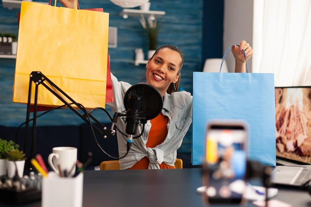 Podcast from social media vlogger with big bags gifts in home studio using professional microphone. creative content creator influencer recording online giveaway talk show for subscribers audience