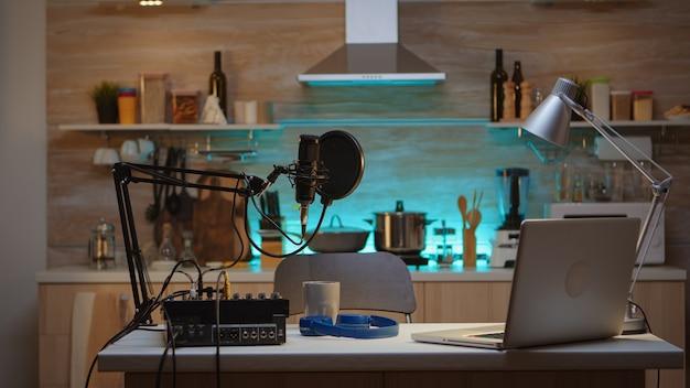 전문 방송 장비를 갖춘 주방의 팟캐스트 홈 스튜디오. 프로덕션 마이크를 사용하여 소셜 미디어 콘텐츠를 녹음하는 인플루언서. 디지털 웹 인터넷 스트리밍 스테이션