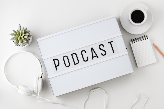 Podcast word on lightbox with headphones on white table