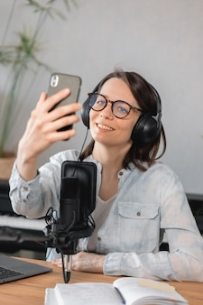 Podcaster는 마이크와 헤드폰 백인으로 팟캐스트를 녹음하는 유럽 여성의 콘텐츠를 만듭니다.