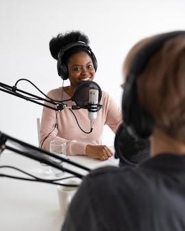 헤드폰과 마이크를 가진 팟캐스터 아프리카계 미국인 및 유럽 여성