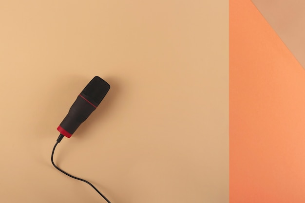 Podcasting concept  microphone at bloggers workplace on a combined beige background