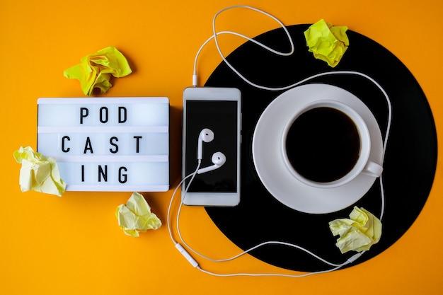 ポッドキャスティングのレタリング。ビニールの記録にあるブラックコーヒーのカップ。スペースをコピーします。音楽を聴く。レトロなスタイル。ポッドキャスト。ヘッドホン付き携帯電話。