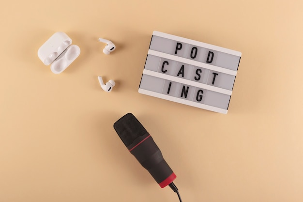 Podcasting lettering next to microphone and wireless headphones at workplace on beige background