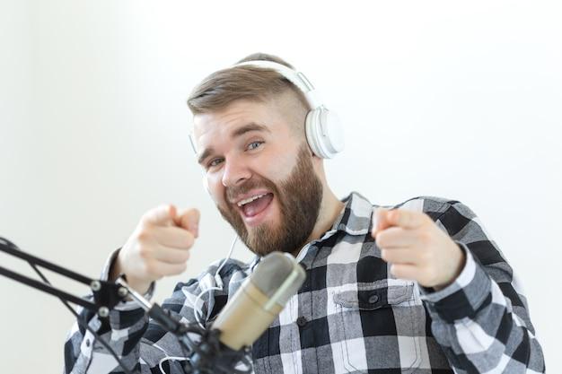팟캐스팅, 음악, 라디오 개념 - 마이크와 큰 헤드폰을 가진 행복한 사람.