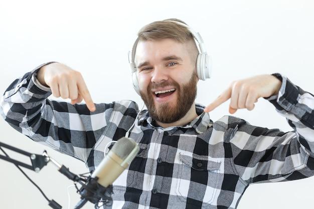 ポッドキャスティング、音楽、ラジオのコンセプト-マイクと大きなヘッドフォンを持った幸せな男