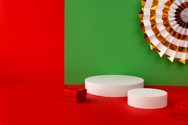 Podium with paper fan on red and green creative background.