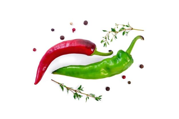 緑と赤の唐辛子のポッド、タイムの2つの小枝と白い背景で隔離の色の唐辛子のエンドウ豆