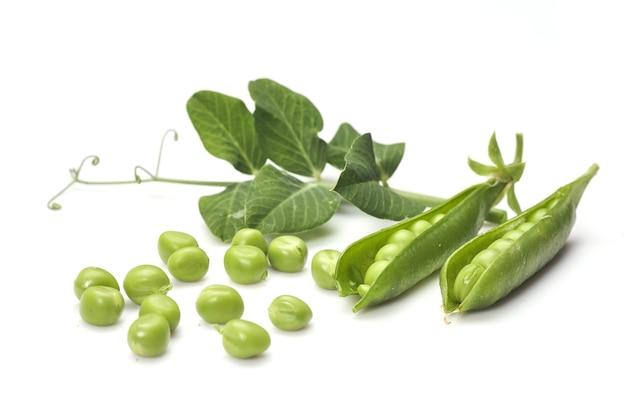 Стручки зеленого горошка с листьями, изолированные на белом фоне