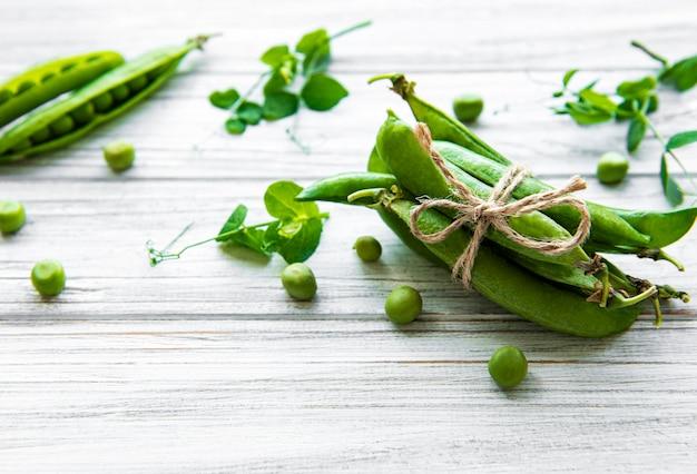 白い木製の背景にエンドウ豆の葉とグリーンピースのポッド。自然食品。