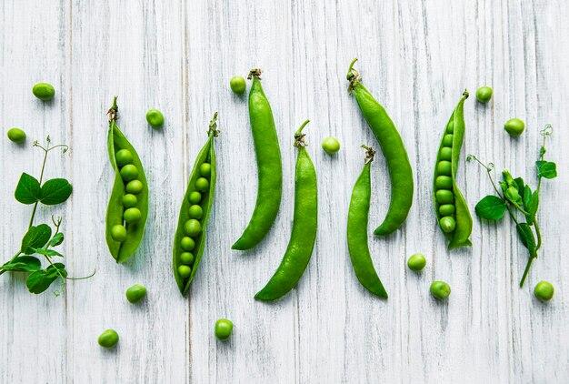 白い木の表面にエンドウ豆の葉を持つグリーンピースのポッド。自然食品。