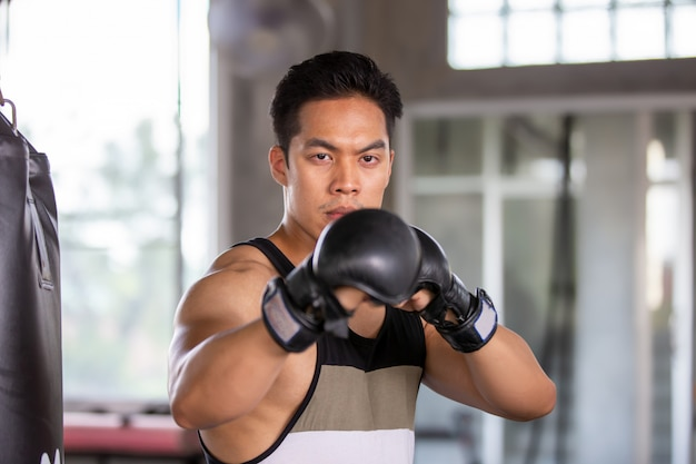 Poeple exercise in fitness gym, man boxing