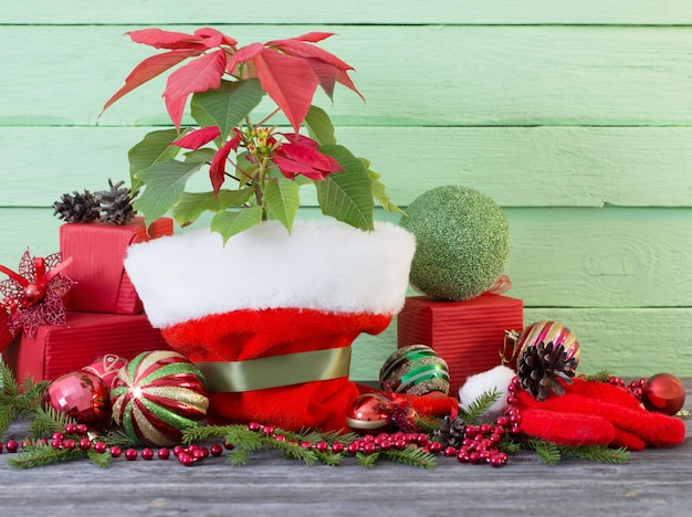 Poinsettia with christmas balls on wooden table